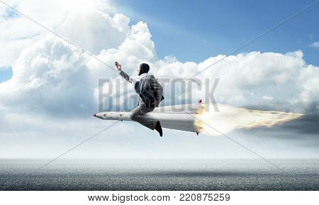 Conceptual image of young businessman in suit flying on rocket above asphalt road with blue cloudy sky on background.