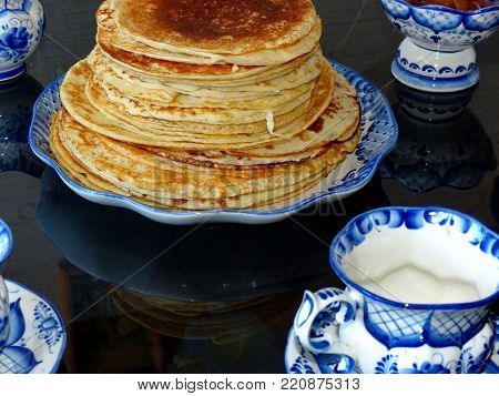Russian blini (pancakes) on a plate Gzhel. Maslenitsa is an Eastern Slavic traditional holiday. Gzhel-Russian folk craft of ceramics and production porcelain and a kind of Russian folk painting.
