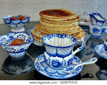 Tableware in the style of Gzhel against the background of traditional Russian pancakes (blini). Gzhel-Russian folk craft of ceramics and production porcelain and a kind of Russian folk painting