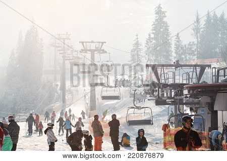 BUKOVEL, UKRAINE - DECEMBER 2016: skiers and snowboarders going uphill on a chairlift in the beautiful morning sunlight
