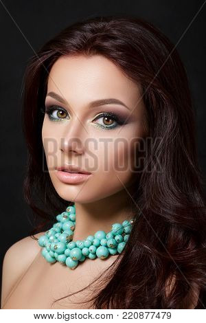 Portrait of young beautiful woman with evening make up wearing blue necklace. Model posing over dark background. Smokey eyes with eyeliner. Classic makeup concept. Studio shot.
