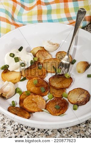 roasted potato slices with spring onion, sour cream and rosemary on a deep white plate
