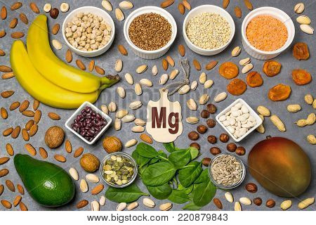 Food is source of magnesium (Mg). Various natural food rich in vitamins. Useful food for health and balanced diet. Prevention of avitaminosis. Small cutting board with name of magnesium. Top view