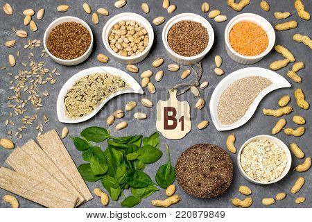 Food is source of vitamin B1. Various natural food rich in vitamins. Useful food for health and balanced diet. Prevention of avitaminosis. Small cutting board with name of vitamin B1. Top view