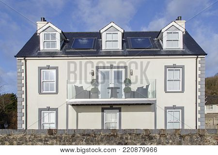Amroth, UK: January 01, 2018: A large detached newly built house with a balcony on the coast road through the seaside village of Amroth in South Wales.