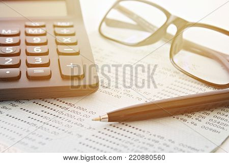 Business, finance, savings, investment or accounting concept : Savings account passbook or financial statement, eyeglasses and pen on table