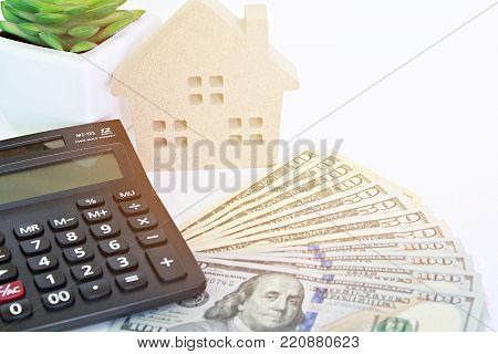 Business, finance, investment, property ladder or mortgage concept ; Wood house model, American dollars cash money and calculator on table