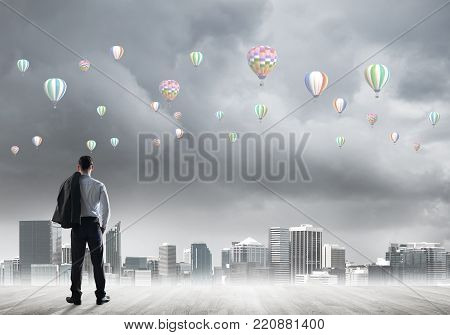 Businessman standing with back and looking at aerostats flying in air