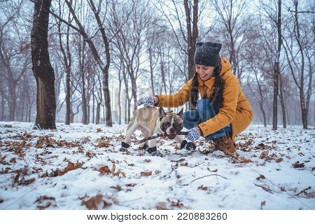 woman playing with french bulldog in winter park