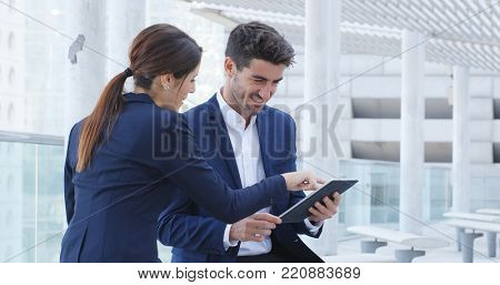 Business people discuss on digital tablet computer outside office