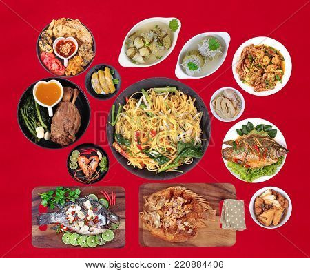 Food to respect God of fortune in the Chinese new year, such as fish, pork, shrimp, crab, bamboo shoots, tofu, desserts and fried yellow noodle in  Chinese style placed on red velvet cloth. (Isola