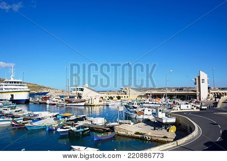MGARR, GOZO, MALTA - APRIL 3, 2017 - Colourful fishing boat moored in the harbour with the Gozo ferry moored in the port to the rear, Mgarr, Gozo, Malta, Europe, April 3, 2017.