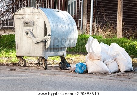 Garbage in the city. White plastic bags full of garbage on the street near the metal dumpster can littering and polluting the city