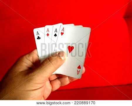 Poker hand holding 4 aces in a red velvet background