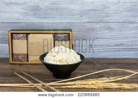 Rice in a black bowl on wood table with various rice in paper box.