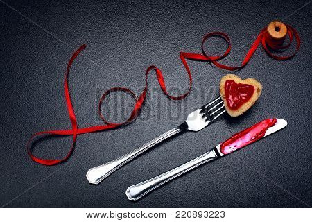 Inscription, word love of red satin ribbon and heart of toast bread with red jam on fork and knife with jam.Valentine day background.Love concept.On dark stone background.Creative.Love backgound