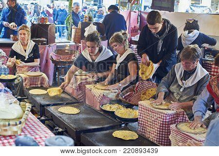 San Sebastian, Basque country, Spain - December 21, 2017: Basque farmers (Baserritarras) making Talos, basque tortilla with txistorra (fresh chorizo) in the Santo Tomas fair, on Saint Thomas's day.