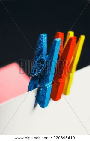 Close up of a note paper and clothes pegs on a black background