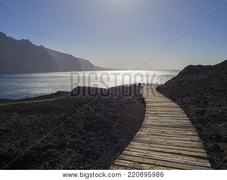wooden planks path leading to the sea shore with view on hight lava cliffs los gigantes on Punta de Teno cape on west Tenerife canary island with lava rock blue sea and clear summer sky Contre-jour against daylight