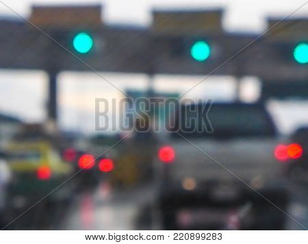blur image - many cars at the front of toll booths in the rainy day