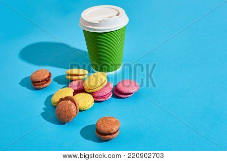 Hot coffee in green paper cup with white lid and macaroons on blue background with shadow, blurred and soft focus image. Still life. Copy space