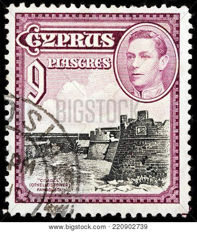 LUGA, RUSSIA - OCTOBER 17, 2017: A stamp printed by CYPRUS shows portrait of King George VI and view of Citadel (Othello's Tower) in Famagusta - city on the east coast of Cyprus, circa 1938