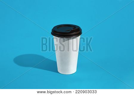 Hot coffee in white paper cup with black lid on blue background with shadow, blurred and soft focus image. Still life. Copy space