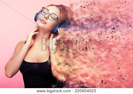 Conceptual image of woman listening to music while she is being dispersed in small particles from the feelings she gets from the music. Imagination and creativity. Conceptual music poster