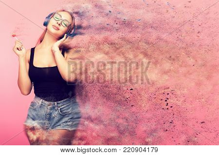 Conceptual image of sexy woman listening to music and holding a lollipop in hands while she is being dispersed in small particles cause the music is giving her a great vibe. Pop art conceptual image