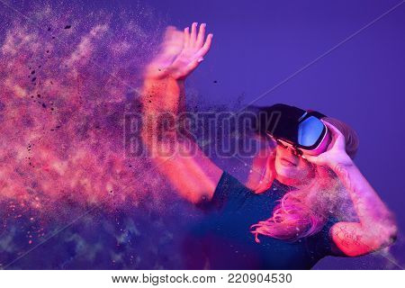 Conceptual image of woman wearing VR headset and being blown away by the virtual reality. Blending imagination with reality