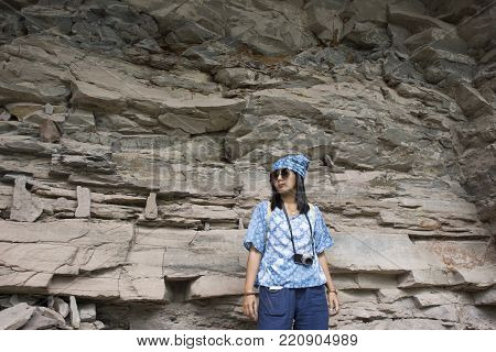 Thai women travel and posing at Rock art includes both humanoid and animal figures on cliffs above the Mekong estimated to be 3,000 years old at Pha Taem National Park in Ubon Ratchathani, Thailand