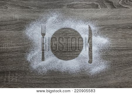 on a wooden background with powdered powder snow covered with silhouette plate fork knife appliances