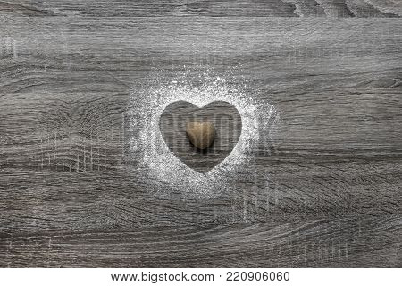 on a wooden background with powdered powder snow a silhouette of the heart is poured and in the center lies a cookie in the form of a heart