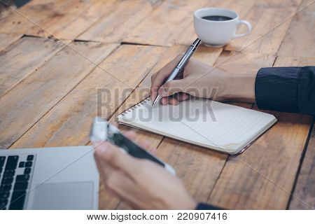 Close up businessman write notebook and using cellphone on wood table.