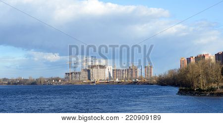 View of Neva river and under construction houses on the outskirts of St. Petersburg at spring day, Russia.
