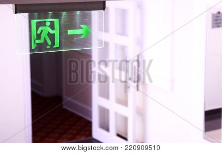 Green illuminated fire exit signin the corridor