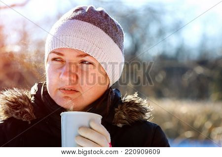 Portrait of young woman drinking tea outdoors at winter street. beautiful woman drinking tea on the street in winter