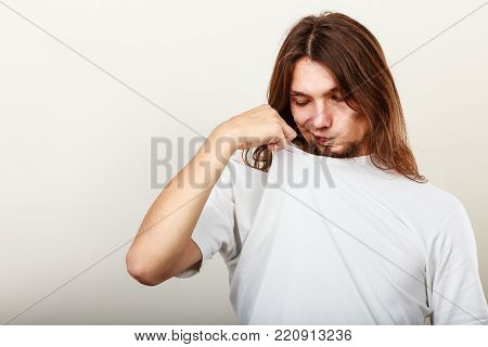 Expression of very bad smell. Young long haired sweaty man making hand gesture. Sweating concept.