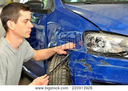 Man inspecting car damage after an accident.