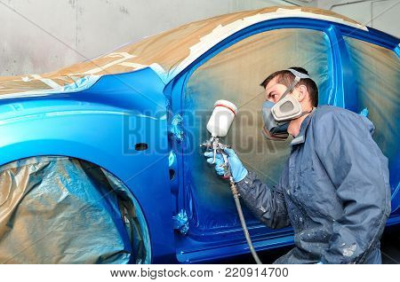Professional car painter working over a blue car.