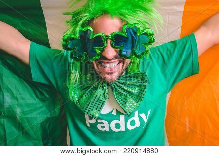 Portrait of a man holding the Irish flag while wearing Saint Patrick's day accessories