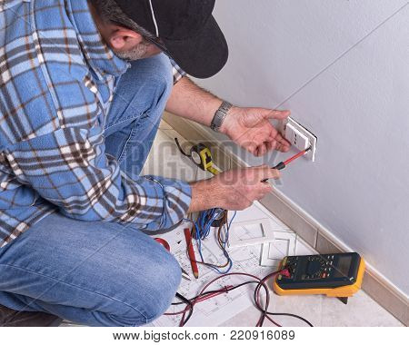 Electrician uses insulated screwdriver to mount electrical outlet plate.