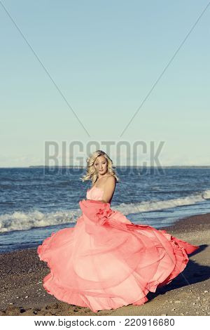woman in red tulle dress dancing at the beach