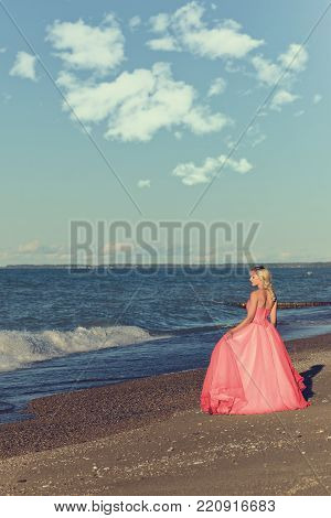 woman in red tulle evening dress by ocean