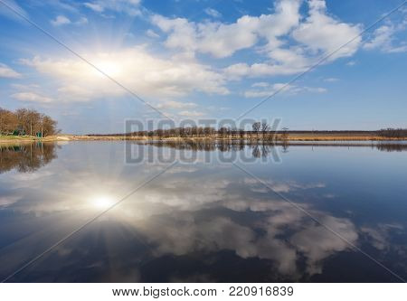 Natural landscape, tree without leaves, river, shore, forest, river grass, reflection many trees blue sky ravines