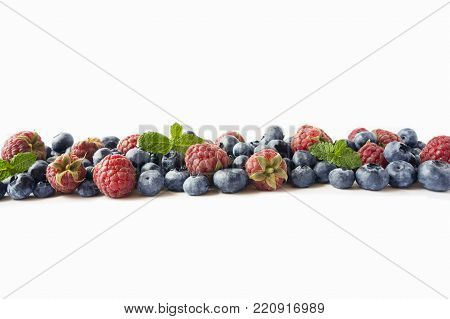 Black-blue and red berries. Ripe raspberries, blueberries with mint on white background. Berries with copy space for text. Background berries. Various fresh summer berries isolated on a white.