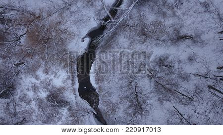 Top down aerial drone image of a river in a forest in the middle of winter.  No leaves on the trees and snow covering the ground.