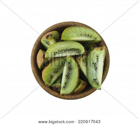 Kiwi slices in a wooden bowl with copy space for text. Ripe and tasty kiwi isolated on white. Kiwi fruit on a white background. Top view with copy space.