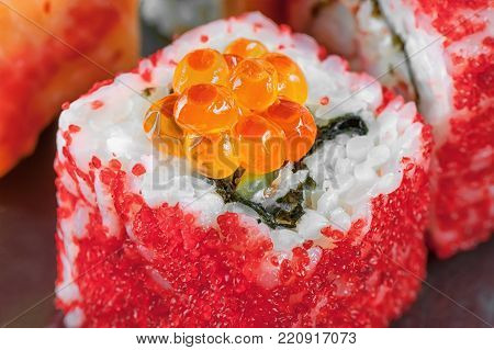 California rolls with salmon ROE and flying fish with eel and Philadelphia cheese closeup. Macro. The horizontal frame.