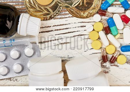 Pills and medals on wooden background. Painkillers and dope for sportsmen. Cheating or price of victory.